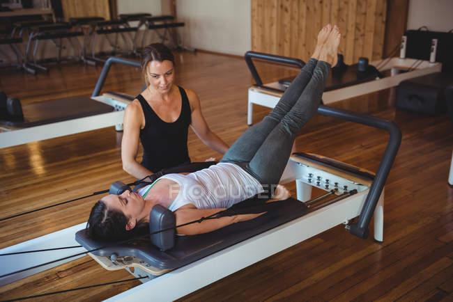 Тренер помогает женщине во время занятий пилатесом в фитнес-студии — стоковое фото