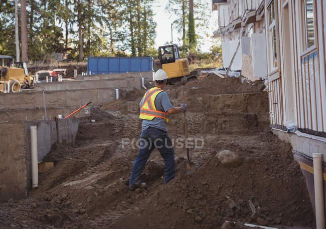 Будівництво працівник працює з лопатою на будмайданчик — стокове фото