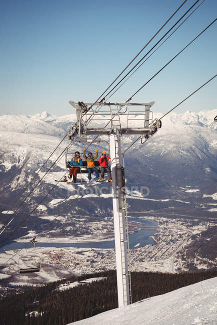 Low angle view of three skiers travelling in ski lift at ski resort — Stock Photo