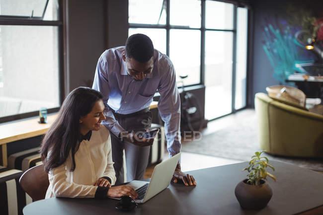 Homme d'affaires et un collègue discutant sur ordinateur portable et téléphone mobile au bureau — Photo de stock