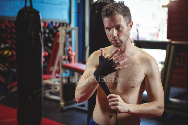 Portrait of confident boxer wearing black strap on wrist in fitness studio — Stock Photo