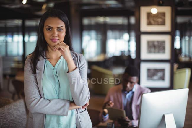 Ritratto di donna d'affari in piedi alla scrivania in ufficio — Foto stock
