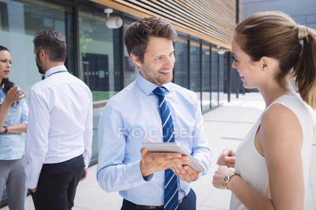 Businessman and colleague discussing over digital tablet outside office building — Stock Photo