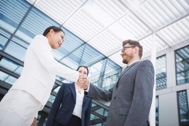 Homme d'affaires, se serrant la main avec une collègue au bureau — Photo de stock