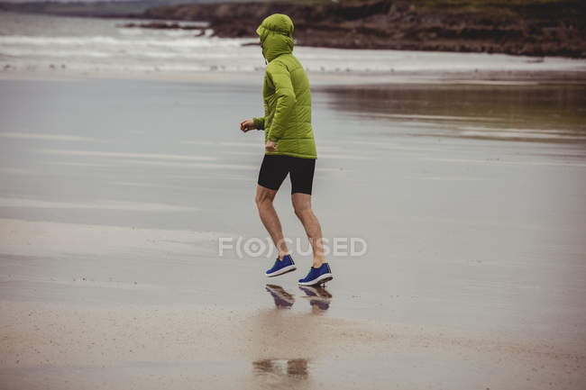 Rear view of athlete running on the beach — Stock Photo