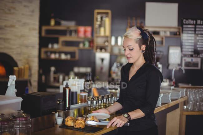 Muffin de servindo de garçonete em uma placa no balcão no café — Fotografia de Stock