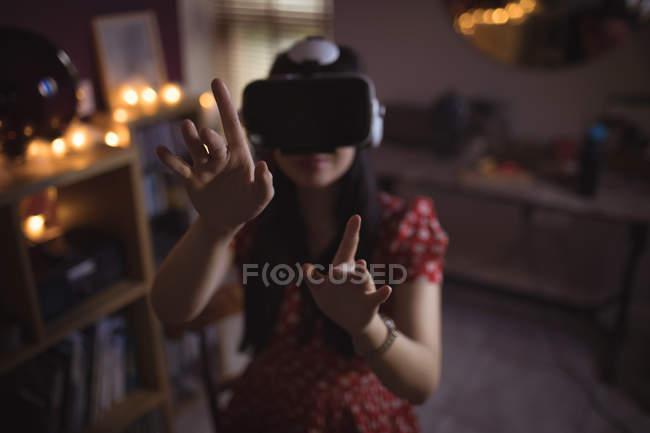 Femme gestuelle tout en utilisant un casque de réalité virtuelle à la maison — Photo de stock