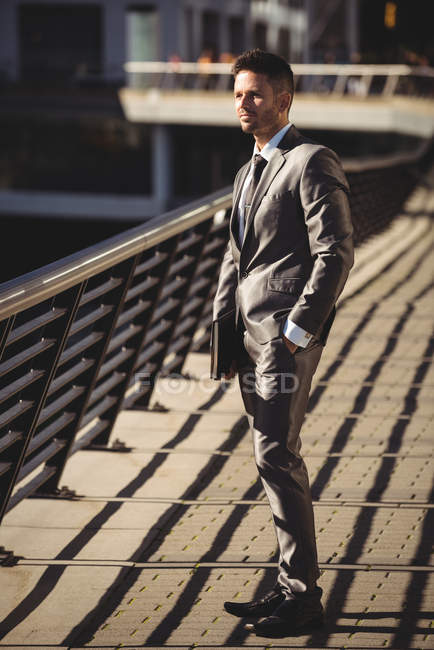 Businessman with a diary standing at office terrace in daytime — Stock Photo