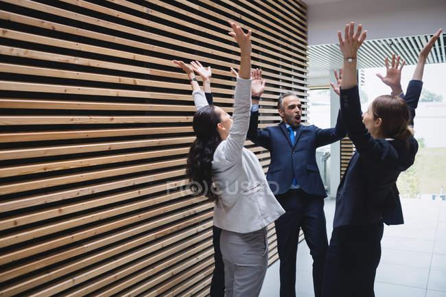 Pessoas de negócios com as mãos levantadas no escritório — Fotografia de Stock