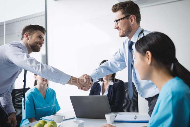 Estrechar las manos unos a otros en la reunión en sala de conferencias de médicos - foto de stock