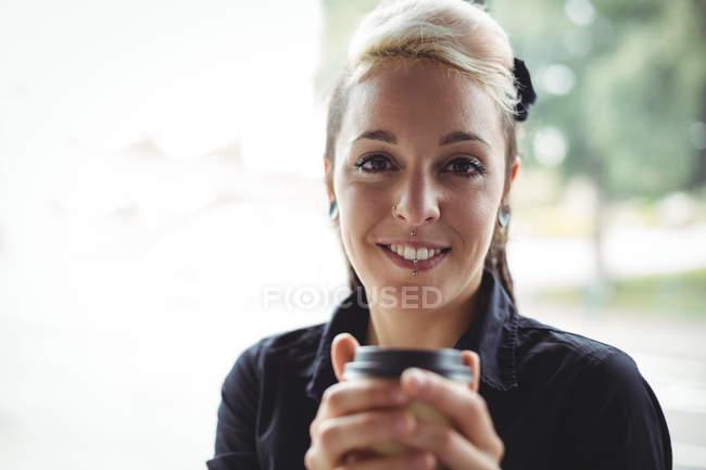Retrato de mulher segurando copo de café descartável no café — Fotografia de Stock