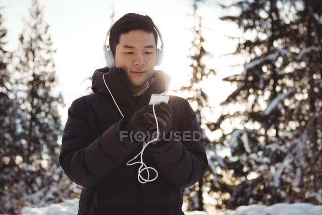 Людина, що слухати музику в навушниках з смартфона під час зими — стокове фото