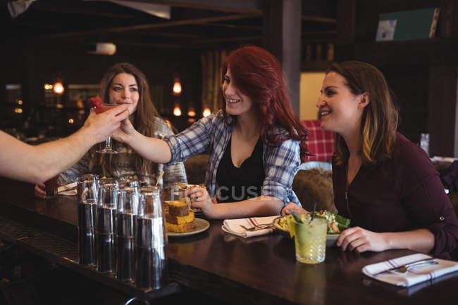 Bar servant des cocktails aux clients dans le bar — Photo de stock