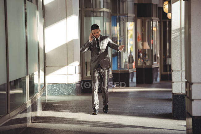 Businessman talking on mobile phone while walking in office building corridor — Stock Photo