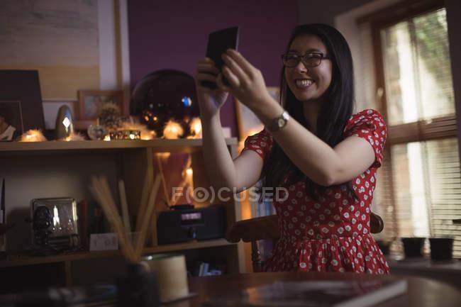 Lächelnde Frau nehmen Selfie auf Handy zu Hause — Stockfoto