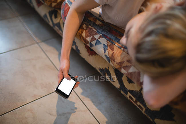 Woman lying and using mobile phone on couch in living room at home — Stock Photo