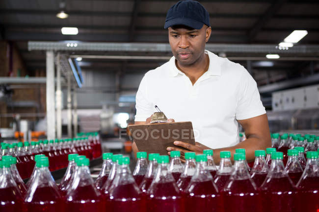 Selbstbewusster männlicher Arbeiter schreibt in Fabrik auf Klemmbrett — Stockfoto