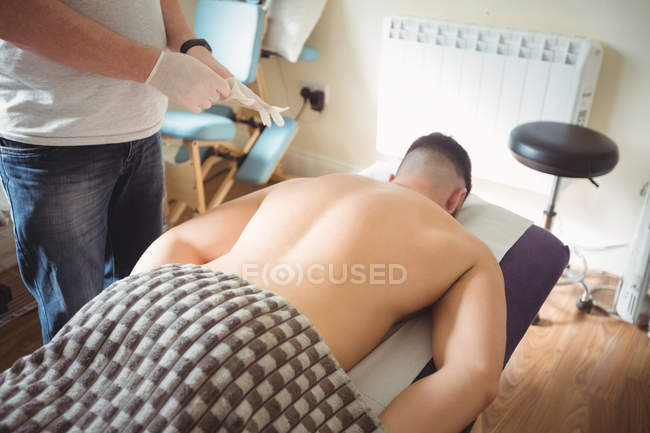 Physiotherapist wearing gloves to performing dry needling on patient in clinic — Stock Photo