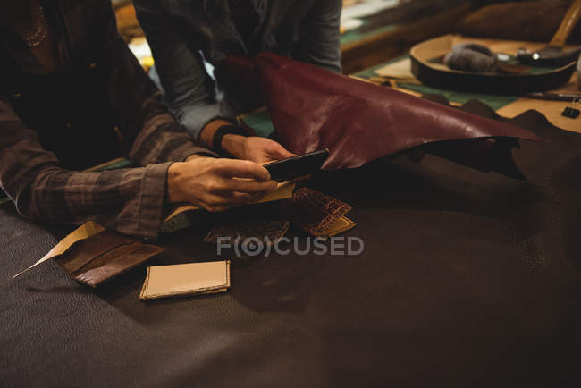 Craftswomen discussing over a sheet of leather in workshop — Stock Photo