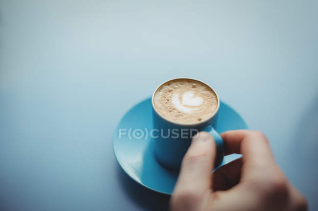 Рука держа чашку кофе на синем фоне — стоковое фото