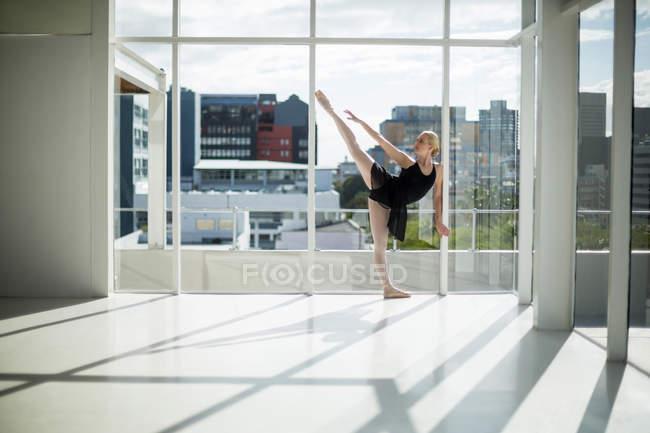 Балерина растягивается на стене во время репетиции балетного танца в студии — стоковое фото