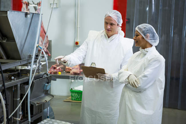 Technicians examining meat processing machine at meat factory — Stock Photo