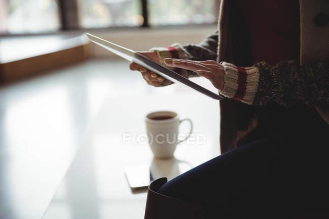 Mittelteil der Frau nutzt digitales Tablet beim Kaffee zu Hause — Stockfoto