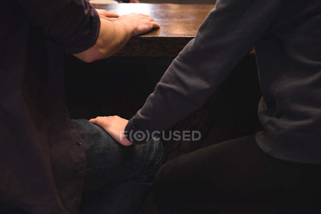 Mid section of romantic couple sitting on stools at bar counter — Stock Photo