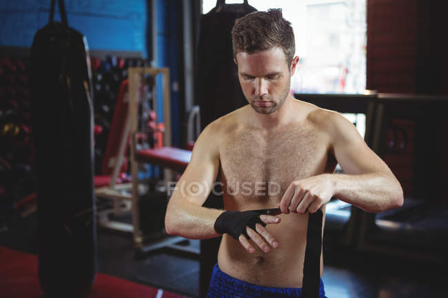 Confident boxer wearing black strap on wrist in fitness studio — Stock Photo