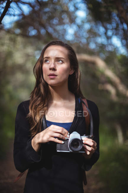 Beautiful woman standing with camera in forest — Stock Photo