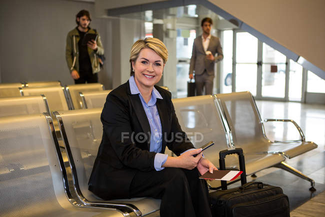 Businesswoman with passport, boarding pass and luggage sitting in waiting area at airport terminal — Stock Photo
