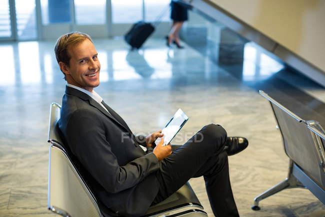 Портрет бизнесмена с цифровым планшетом в зале ожидания терминала аэропорта — стоковое фото