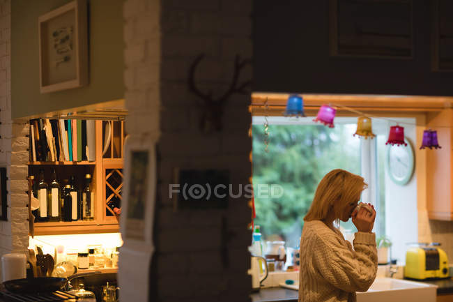 Woman having coffee in kitchen at home — Stock Photo
