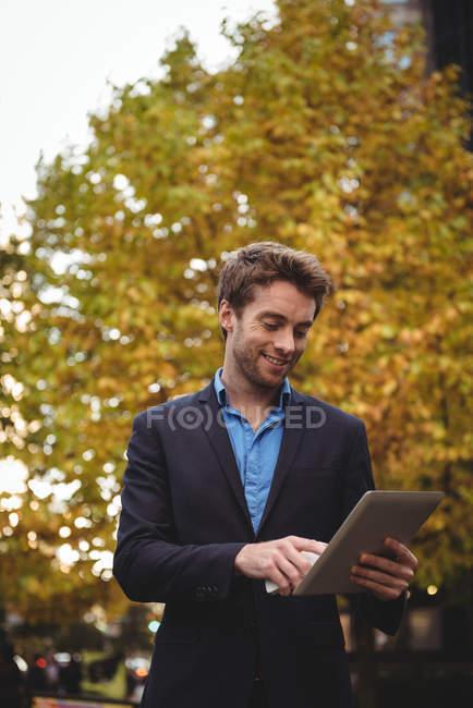 Uomo d'affari sorridente che tiene il telefono cellulare e utilizza tablet digitale sulla strada — Foto stock