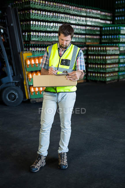 Full length of confident male worker writing on clipboard in warehouse — Stock Photo