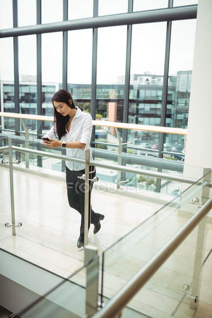 Businesswoman leaning on railing and using mobile phone at office corridor — Stock Photo