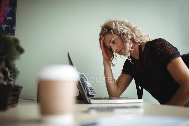Mulher de negócios frustrada trabalhando no laptop no escritório com café na mesa — Fotografia de Stock