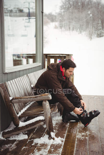 Man putting his ski boot on at a ski resort — Stock Photo