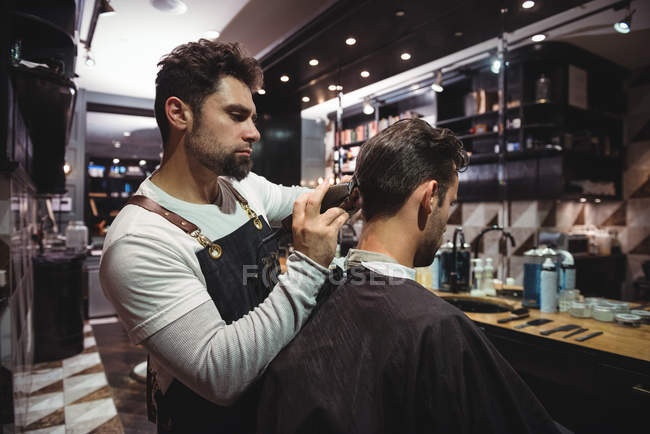 Barbiere maschio taglio capelli cliente con trimmer in barbiere — Foto stock