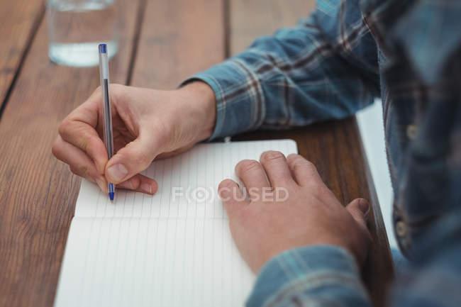 Закри людина сидить в бюро, писати щоденник вдома — стокове фото