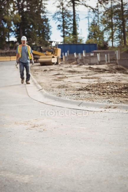 Працівник будівництва, йдучи на будмайданчик — стокове фото