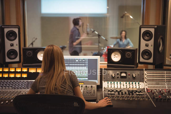 Rear view of audio engineer using sound mixer in recording studio — Stock Photo