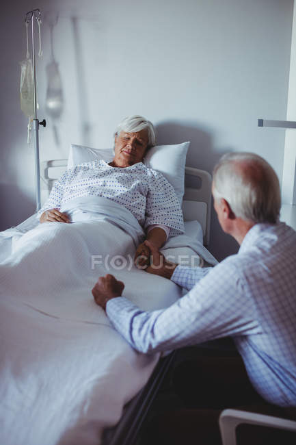 Ill woman sleeping on bed while worried man sitting beside her bed in the hospital — Stock Photo