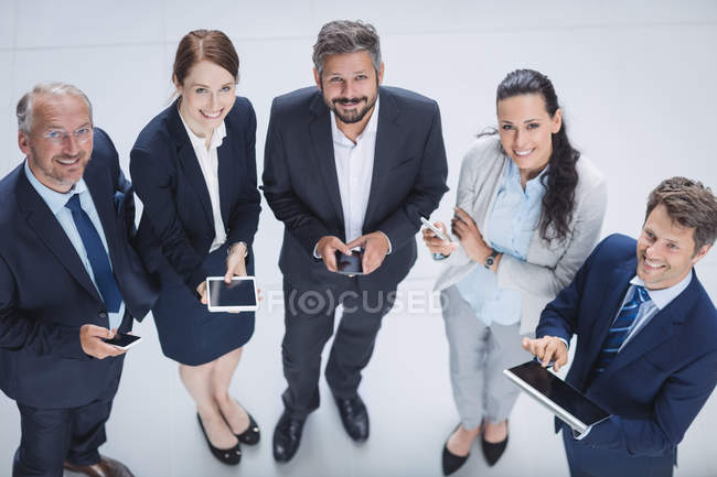 Portrait of business people using mobile phone and digital tablet in office — Stock Photo