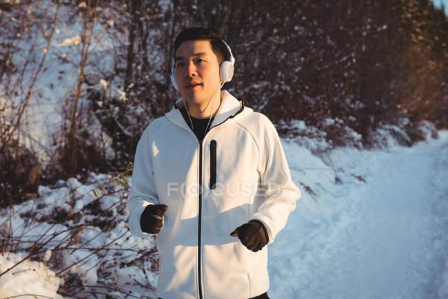 Uomo che ascolta musica in cuffia mentre fa jogging in un sentiero innevato durante l'inverno — Foto stock