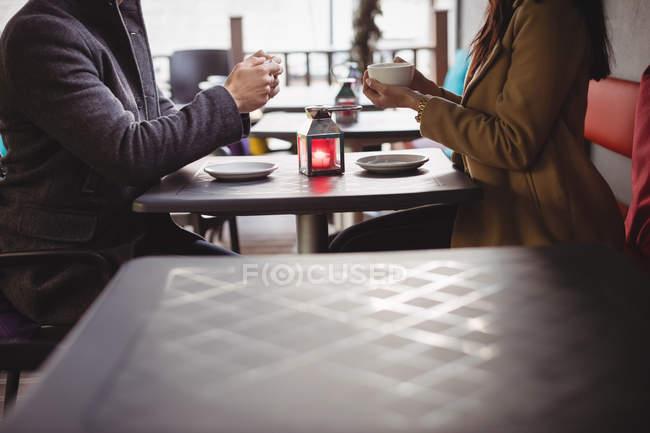 Mittelteil des Paares hält Kaffeetassen im Restaurant — Stockfoto