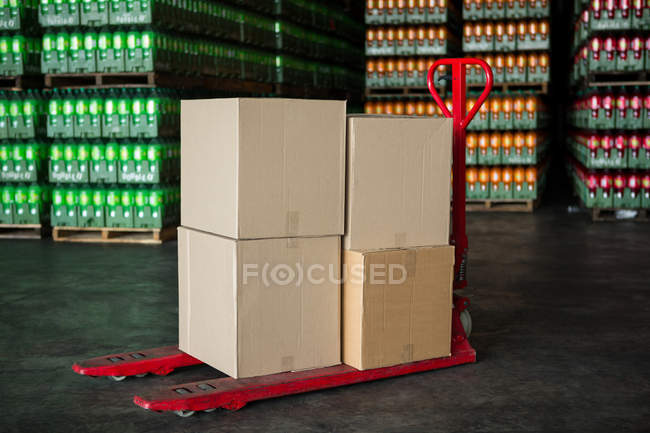 Картонные коробки на тележке на соковом заводе — стоковое фото