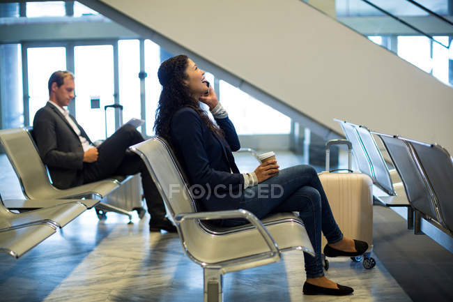 Female commuter with coffee cup talking on mobile phone in waiting area at airport terminal — Stock Photo