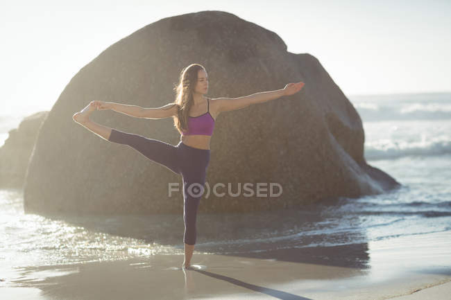 Beautiful woman performing stretching exercise on beach on a sunny day — Stock Photo