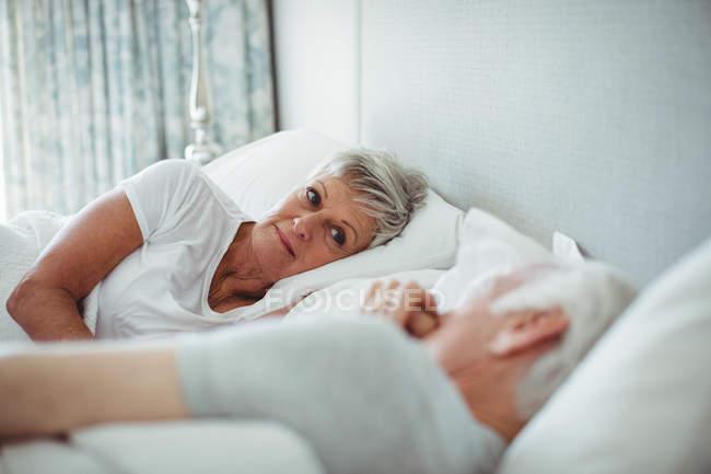 Senior pareja acostado en cama en el dormitorio - foto de stock